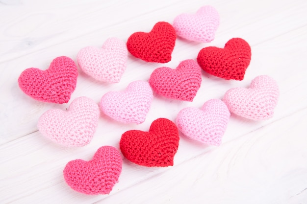 A lot of pink knitted hearts on a white wooden background. valentine's day. Premium Photo