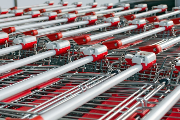 A lot of shopping carts with locks standing inserted one into the other. Premium Photo