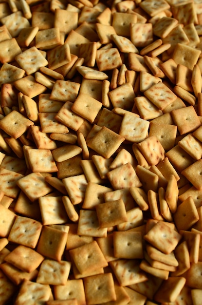 A lot of small cookies are square shaped. a pattern of a yellow salt cracker. background image with salted pastry Premium Photo