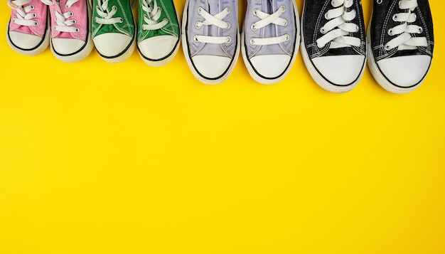 Lot of textile worn sneakers of different sizes on a yellow background Premium Photo