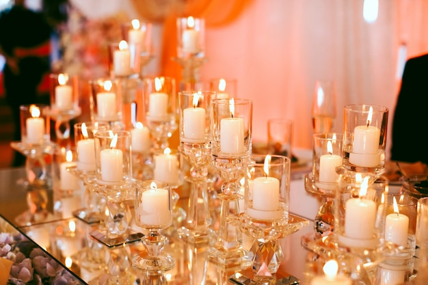 Lots of burning white candles on the table Free Photo