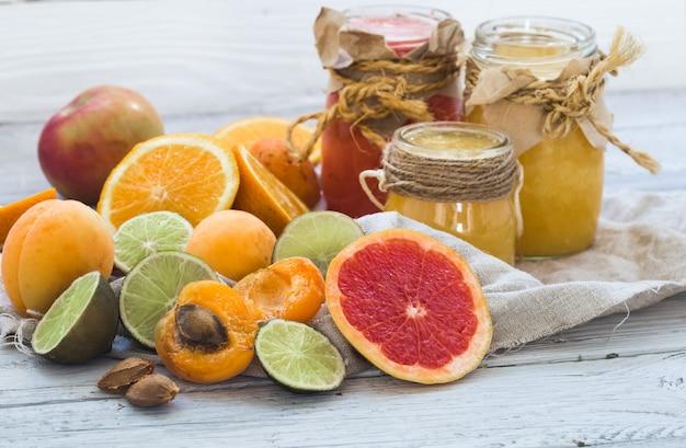 たくさんの新鮮な果物、美しい木製の背景にカット、新鮮な果物の飲み物、ジャム、おいしい、健康食品 無料写真