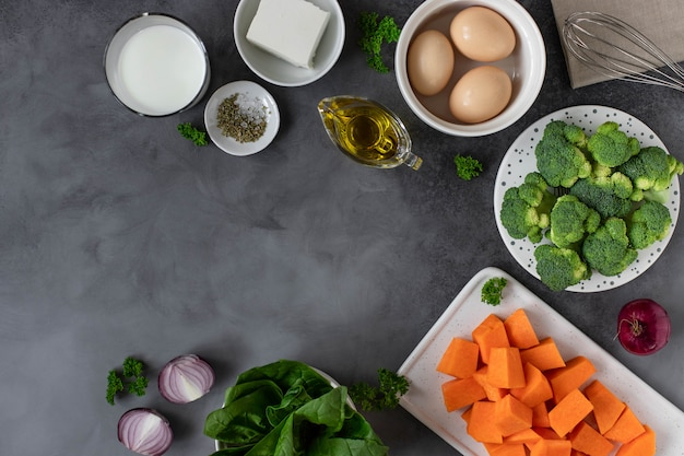 Lots of raw vegetables, spices and olive oil. cooking healthy food concept. dark background, copy space Premium Photo
