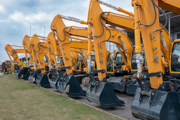 Lots of yellow tractors or excavators at an exhibition Premium Photo