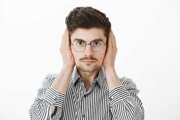 Громкий сосед по комнате отвлекает парня от работы фрилансером. портрет обеспокоенного раздраженного обычного европейского коллеги-мужчины в модных очках и полосатой рубашке, прикрывающего уши ладонями и серьезно выглядящего Бесплатные Фотографии
