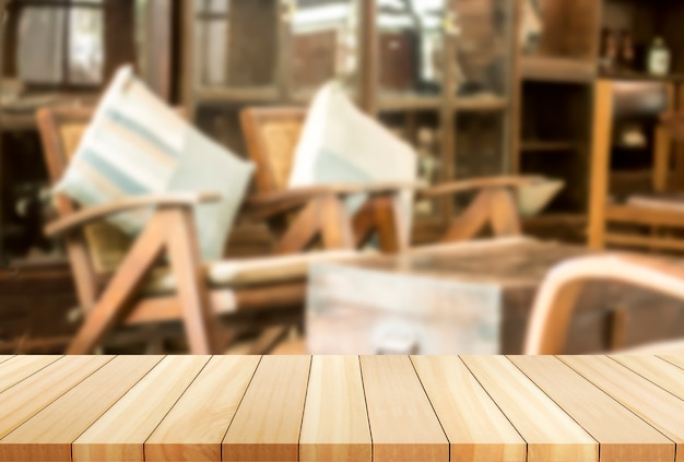 Lounge chairs the image is blurred.wooden board empty table in front of blurred background. Premium Photo