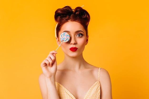 하드 캔디를 들고 사랑스러운 여성 모델. 노란색 공간에 고립 된 롤리팝 영감 된 생강 소녀의 스튜디오 샷. 무료 사진