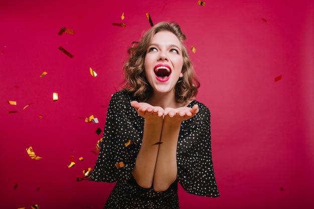색종이 파티에서 긍정적 인 감정을 표현하는 사랑스러운 단발 소녀 무료 사진