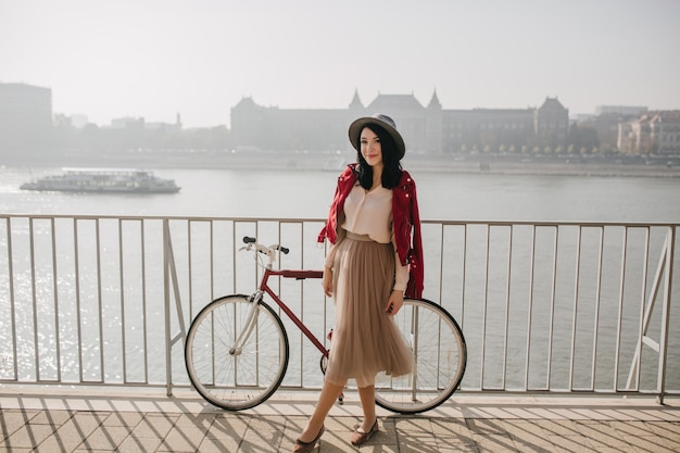 自転車の近くに立っているベージュのスカートの愛らしい女性 無料写真