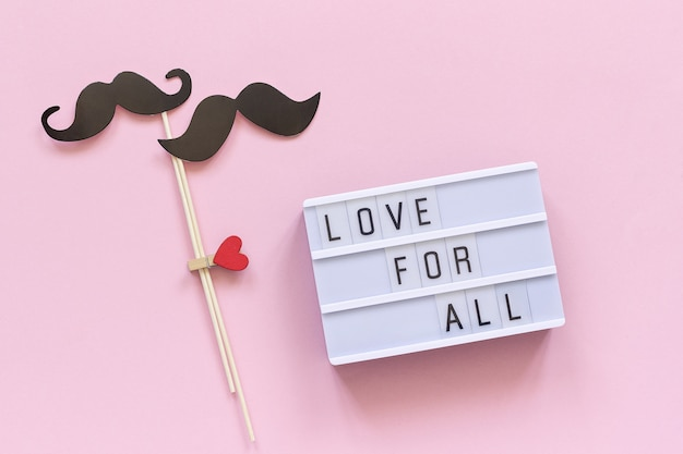 Love for all light box text and couple paper mustache props Premium Photo