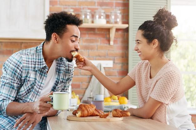 Концепция любви и заботы. прекрасная пара веселится вместе: заботливая женщина кормит мужа круассаном, Бесплатные Фотографии