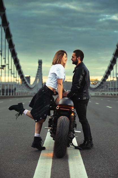 Любовь и романтическая концепция. красивая пара на мотоцикле стоит друг напротив друга посреди дороги на мосту Premium Фотографии