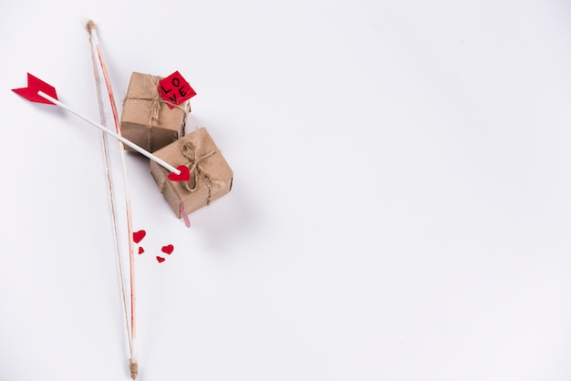 Love arrow with bow and gift boxes on table Free Photo