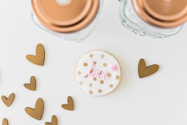 Любовное круглое печенье с сердечками и баночка на белом фоне Бесплатные Фотографии
