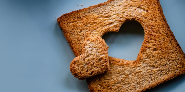 Love concept. burned sliced toasted bread with a shape of heart lay on table Premium Photo