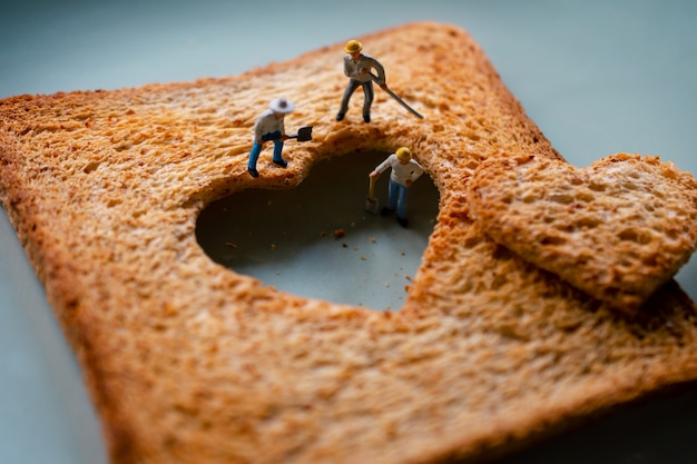 Love concept. sad relationship. group of worker miniature fixing heart Premium Photo