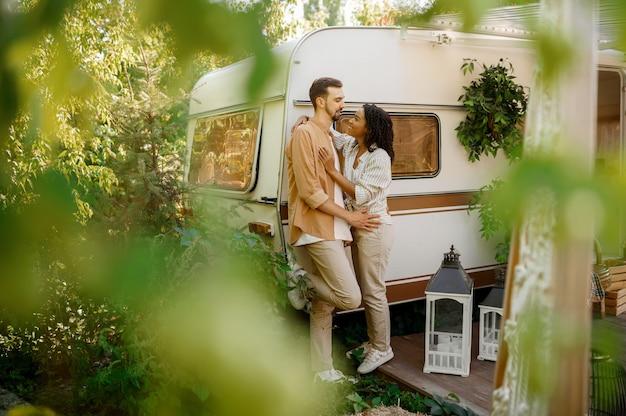 러브 커플은 트레일러에서 캠핑, Rv에서 포용합니다. 남자와 여자는 밴, 캠핑카에서의 낭만적 인 휴가, 캠핑카의 캠핑 레저 프리미엄 사진