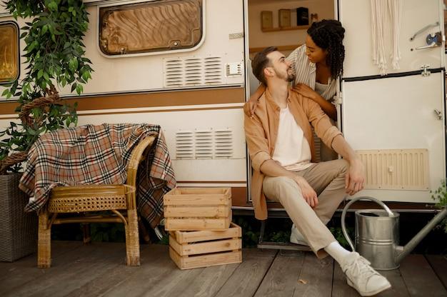 러브 커플 포옹, 트레일러 캠핑. 남자와 여자는 밴, 캠핑카에서의 낭만적 인 휴가, 캠핑카의 캠핑 레저 프리미엄 사진
