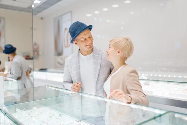 Влюбленная пара смотрит на драгоценности в ювелирном магазине Premium Фотографии
