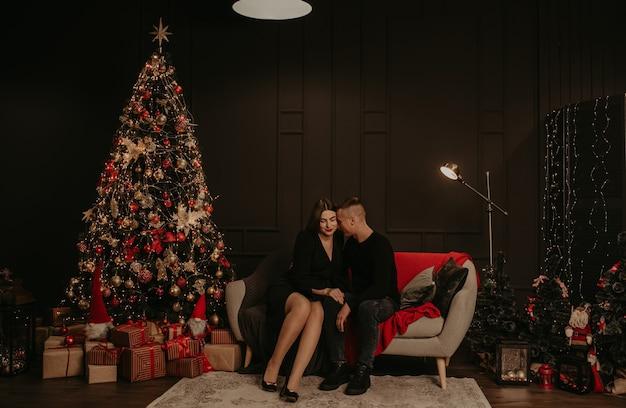Влюбленная пара мужчина и женщина обнимаются и целуются возле елки Premium Фотографии
