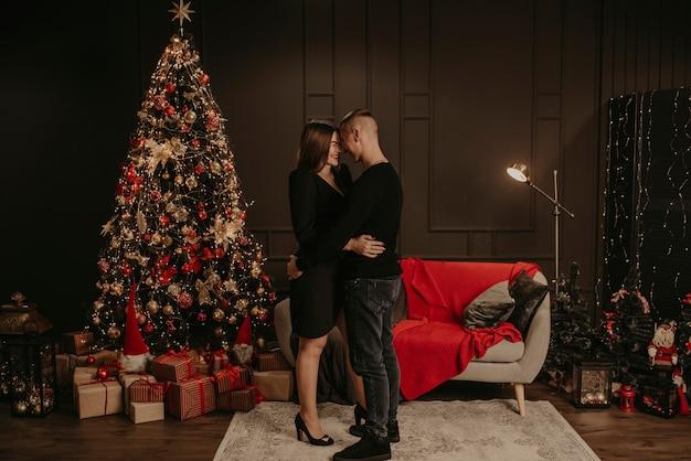 사랑 커플 남자와 여자 크리스마스 트리 근처 키스 포옹 프리미엄 사진