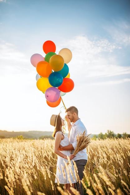 Влюбленная пара с объятиями воздушных шаров в пшеничном поле Premium Фотографии