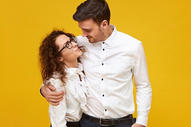 愛、交際、恋愛、関係の概念。情熱を持って彼を見ている彼の美しいガールフレンドを抱きしめる背の高いハンサムな男。孤立した、抱き締めて、抱きしめるポーズをとるかわいいロマンチックなカップル 無料写真