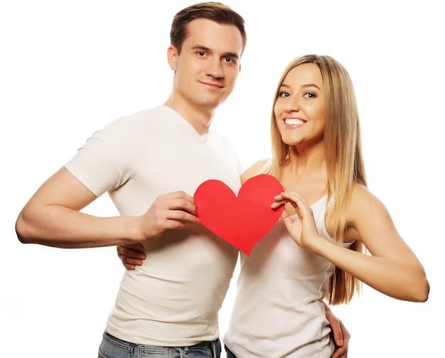 Концепция любви, семьи и людей: счастливая пара в любви держит красное сердце. Premium Фотографии