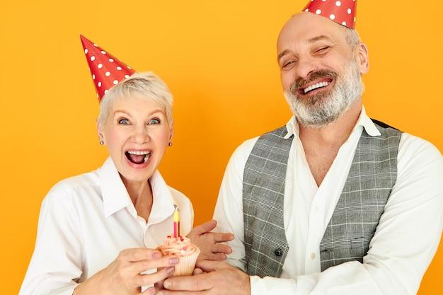 Amore, famiglia, festa, gioia e felicità. bella femmina matura dai capelli corti felicissima che celebra l'anniversario di matrimonio con il marito barbuto, indossando cappelli a cono e soffiando una candela sulla torta della tazza Foto Gratuite