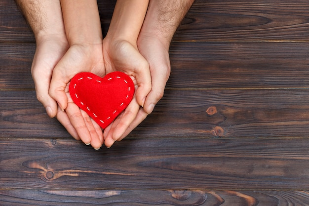 Love, family concept. close up of man and woman hands holding red rubber heart together Premium Photo