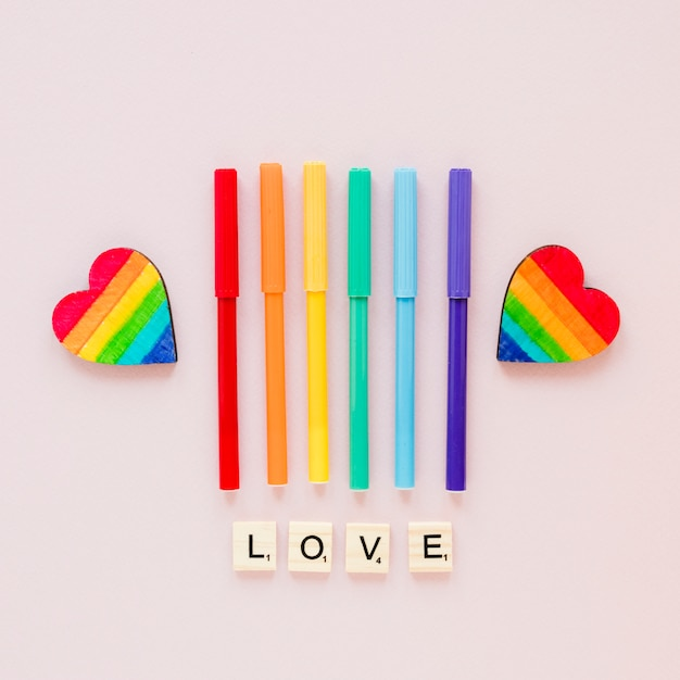 Love inscription with rainbow hearts and felt pens Free Photo