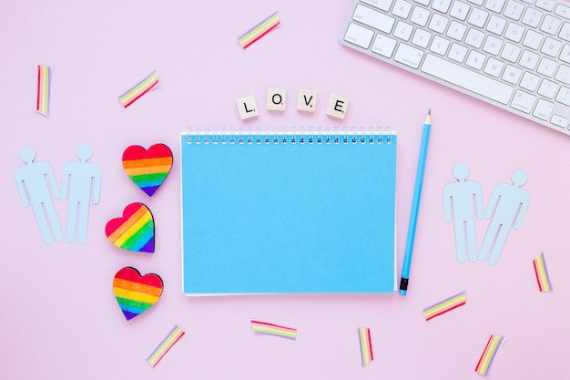 Love inscription with rainbow hearts, gay couples icons and notepad Free Photo