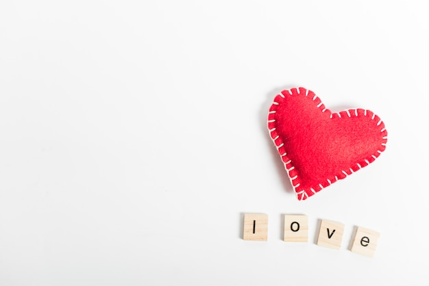 Love inscription with toy heart on table Free Photo