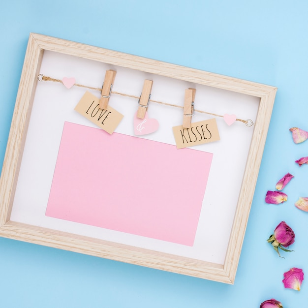 Love and kisses inscription in frame with flower petals Free Photo