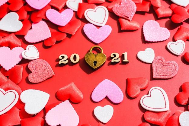 Замок любви на красном фоне с сердечками Premium Фотографии