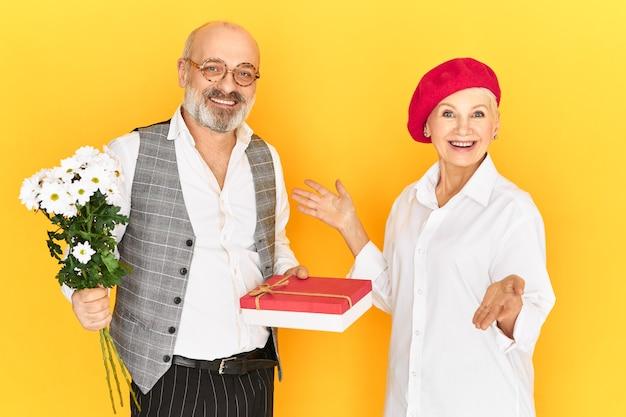 사랑, 로맨스, 사람과 나이 개념. 생일에 그녀의 꽃과 Boxof 과자를주는 매력적인 세련된 여성과 유혹 대머리 머리와 두꺼운 회색 수염을 가진 행복한 노인의 스튜디오 샷 무료 사진