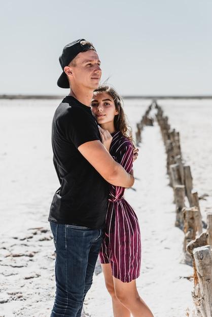 История любви в пустыне, счастливая молодая пара, молодые люди гуляют и держатся за руки, летние каникулы для молодой пары Premium Фотографии