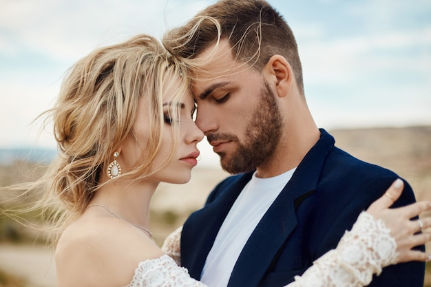 Love story of a woman and a man. loving couple embraces, a beautiful oriental couple. a man in a jacket and a woman in a long luxurious light dress Premium Photo