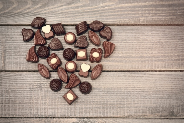 Love symbol full of chocolate candies Free Photo