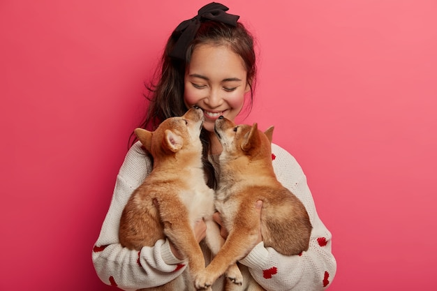 Amore, tenero, caldo sentimento e comprensione senza parole. un'allegra donna coreana riceve il bacio da due cuccioli di razza, non può immaginare la vita senza animali domestici, si diverte con i migliori amici degli animali. Foto Gratuite