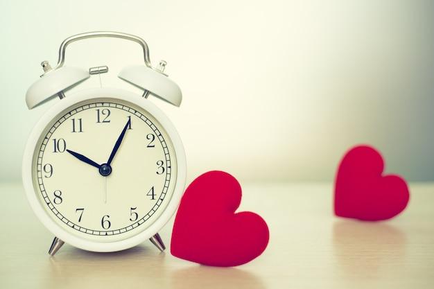 Часы времени любви с красным пространством сердца для текста. Premium Фотографии