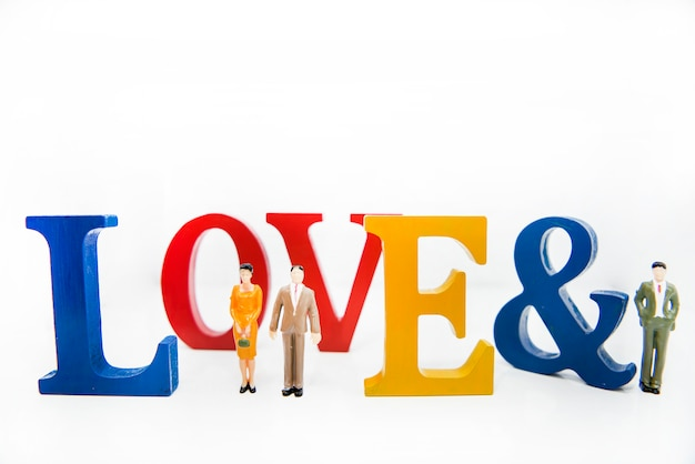 Love triangle. abstract photo of love and lovers. big wooden letters with small plastic people figures. Premium Photo