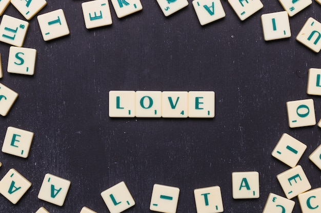Love word arranged on black background surrounded by scrabble letters Free Photo