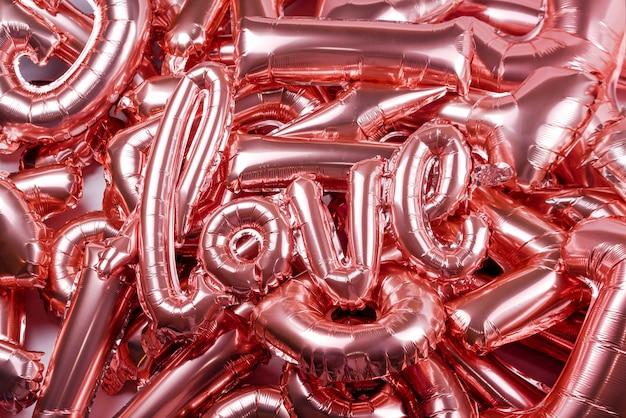 Любовное слово от розового надувного воздушного шара, кладущего на других баллонах. концепция романтики, день святого валентина. любовный воздушный шар из розового золота Premium Фотографии