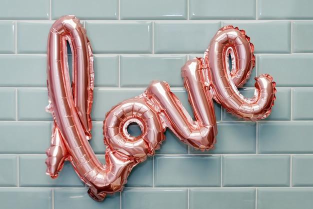 Любовное слово из розового надувного шарика на стене из мятной плитки Premium Фотографии