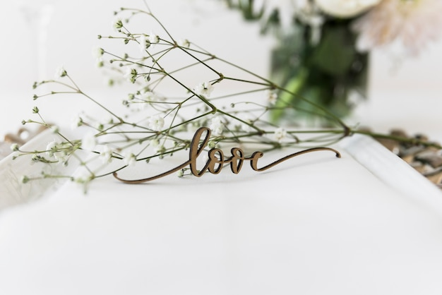 Love word and white flowers on plate Free Photo