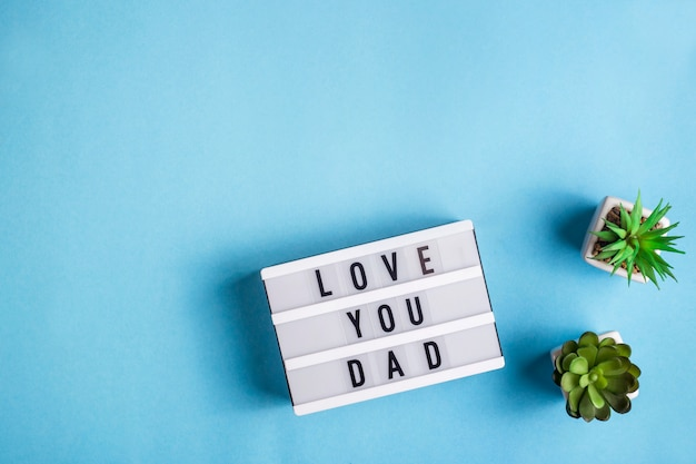 Love you dad is written on a decorative lamp on a blue background Premium Photo