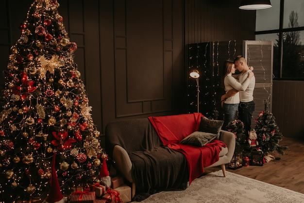 Любовь молодая пара мужчина и женщина обнимаются, целуются возле елки. Premium Фотографии