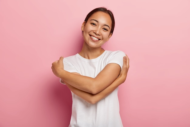 Love yourself. pretty glad asian girl embraces herself, feels comfort and care, tilts head, wears white t shirt, has no make up, isolated over rosy wall, thinks about lover, wants be in his warm arms Free Photo