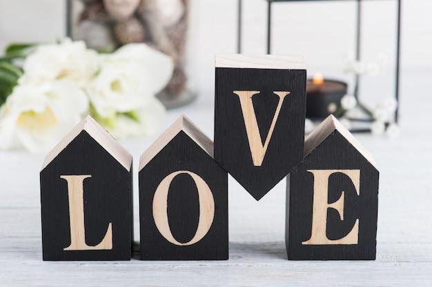 Цветы и зажженная свеча, деревянная буква love Premium Фотографии